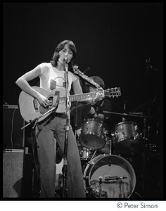 Thumbnail of Joan Baez with guitar, performing on stage at the Harvard Square Theater,             Cambridge, with the Rolling Thunder Revue