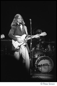 Thumbnail of T-Bone Burnett playing Rickenbacker guitar on stage at the Harvard Square Theater,             Cambridge, with the Rolling Thunder Revue