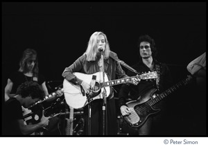 Thumbnail of Joni Mitchell performing at the Harvard Square Theater, Cambridge, with the             Rolling Thunder Revue From left: Mick Ronson, unidentified videographer, Mitchell, Rob Stoner