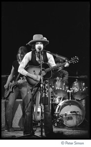 Thumbnail of Bob Dylan performing at the Harvard Square Theater, Cambridge, with the             Rolling Thunder Revue Mick Ronson (guitar) in the rear