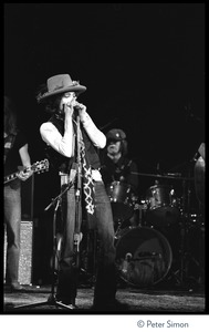 Thumbnail of Bob Dylan performing on harmonica at the Harvard Square Theater, Cambridge, with the             Rolling Thunder Revue Mick Ronson (guitar, obscured) and Howie Wyeth (drums) in the background