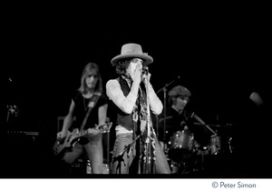 Thumbnail of Bob Dylan performing on harmonica at the Harvard Square Theater, Cambridge, with the             Rolling Thunder Revue Mick Ronson (guitar) and Howie Wyeth (drums) in the background
