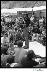Thumbnail of Arlo Guthrie performing at the Newport Folk Festival Full length portrait of Guthrie on a small stage, playing acoustic guitar