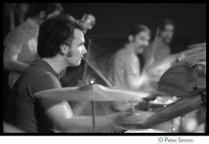 Thumbnail of Bill Kreutzmann playing drums during Grateful Dead concert at the Ark Bob Weir (obscured), Mickey Hart, and Tom Constanten just visible in the background