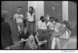 Thumbnail of Group gathered at the stage door entrance, possibly at the No Nukes concert Group includes two members of the Doobie Brothers: Tiran Porter (standing by column), Patrick Simmons (seated with arms crossed)