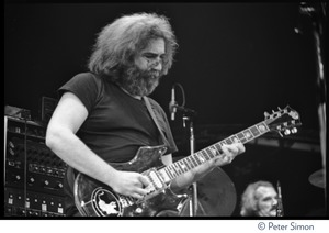 Thumbnail of Jerry Garcia, playing guitar in concert with the Grateful Dead, Radio City Music Hall Garcia in front of sound system, Bill Kreutzmann in background