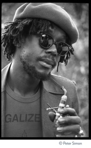 Thumbnail of Peter Tosh: portrait wearing beret, dark glasses, and a Legalize it tee shirt, smoking a pipe