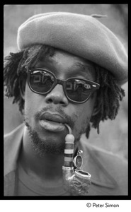 Thumbnail of Peter Tosh: portrait wearing beret, dark glasses, and smoking a pipe