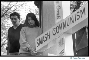 Thumbnail of Richard and Mimi Farina look over the Polish Freedom Fighters' cross marked with 'Smash Communism,' carried by             counter-protesters at the Resistance antiwar rally on the Boston Common