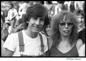 Thumbnail of Graham Nash in overalls standing with Joni Mitchell at the No Nukes protest and concert