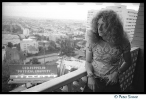 Thumbnail of Robert Plant (Led Zeppelin) on the balcony of his room at the Riot House, with             billboard in the background advertizing the new album, Physical Graffiti