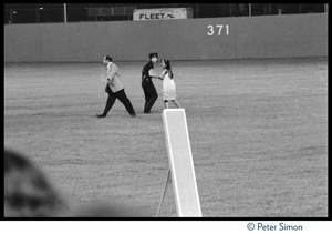 Thumbnail of Policeman confronts a young girl rushing the field at Shea Stadium during the Beatles concert