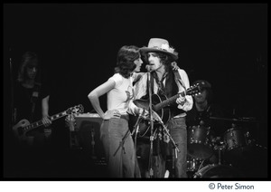 Thumbnail of Joan Baez with arm on the shoulder of Bob Dylan, performing with the Rolling             Thunder Revue at the Harvard Square Theater
