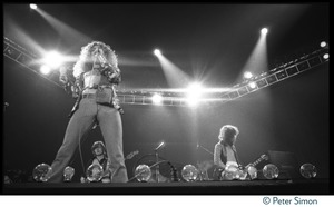 Thumbnail of Robert Plant on stage with Led Zeppelin during their Physical Graffiti tour John Paul Jones (bass) and Jimmy Page (guitar) in background