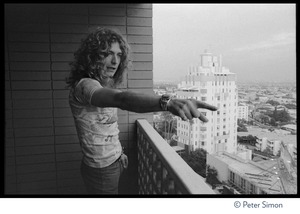 Thumbnail of Robert Plant (Led Zeppelin) looks at Sunset Strip from a balcony at the             Riot House, pointing at a billboard advertising the Physical Graffiti album 'As I took this photo on assignment with Stephen Davis for Atlantic Monthly,             Plant shouted out 'I'm a golden god''
