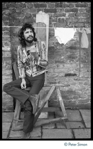 Thumbnail of Cat Stevens: full-length portrait, seated by a laundry line on Carly Simon's             patio