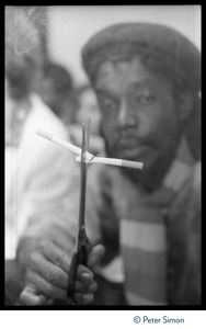 Thumbnail of Peter Tosh holding up two cigarettes with scissors, surrounded by a haze of marijuana smoke, backstage at Saturday Night Live