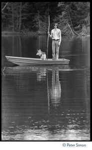 Thumbnail of James Taylor standing in a row boat in a pond at Tree Frog Farm commune, with stick and dog Posed for cover of Taylor's One Man Dog album