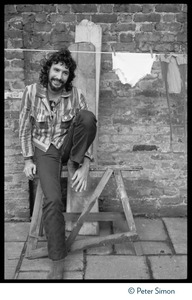Thumbnail of Cat Stevens: full-length portrait, seated by a laundry line on Carly Simon's             back door patio