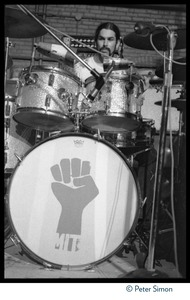 Thumbnail of Mickey Hart (Grateful Dead) performing on drums at MIT during the             student strike against the war in Vietnam and killings at Kent State Hart's bass drum is decorated with the clenched-fist symbol of the student             strike