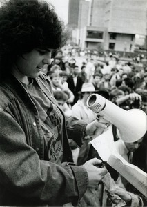 Thumbnail of 'Students protest': speaker in front of crowd at UMass Amherst holding bullhorn, wearing t-shirt             reading 'Put the CIA on trial'