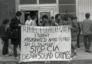 Thumbnail of Protesters in front of Student Union at UMass Amherst holding a banner reading 'Rafael Eduardo Garcia student             assassinated April 14, 1987 in El Salvador. Stop CIA death squad crimes'