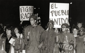 Thumbnail of Anti-racism protesters at UMass Amherst holding placards reading 'Fight racism' and 'El Pueblo Unido'