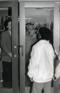 Thumbnail of Woman greeted at door of Whitmore Hall, UMass Amherst, by police officer and official
