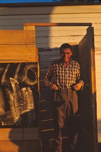 Thumbnail of Unidentified man standing in wood frame structure in sunlight