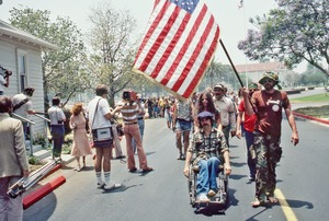 Thumbnail of Gene Dorr holding flag the over Ron Kovic