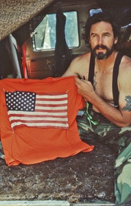 Thumbnail of Gene Dorr holding an orange shirt with a flag