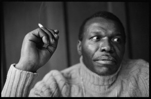 Thumbnail of Elvin Jones: half-length portrait of jazz musician, seated, smoking a cigarette