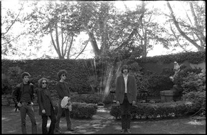 Thumbnail of The  Velvet Underground: (l.-r.) Lou Reed, Maureen Tucker, Doug Yule, and Sterling Morrison standing in a circle garden