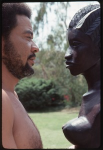 Thumbnail of Bill Withers: Withers shirtless and in profile facing an African bust