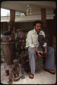 Thumbnail of Bill Withers: Withers surrounded by African sculpture and cupping the breasts of a bust