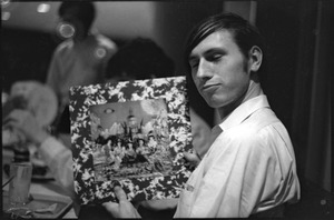 Thumbnail of At the Boston University News Office: man holding copy of Rolling Stones', 'Their Satanic Majesties Request'