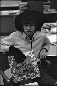 Thumbnail of At the Boston University News Office: Peter Simon wearing hat and glove and holding copy of Rolling Stones', 'Their Satanic Majesties Request'