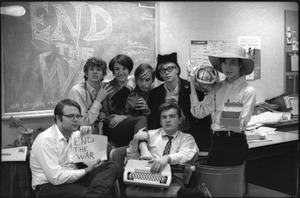 Thumbnail of At the Boston University News Office: staff of BU News, Don McClean holding sign, Peter Simon top left, unidentified woman, unidentified man, Clif Garboden, Ed Siegel, and Joe Pilati in front with typewriter, December 1967