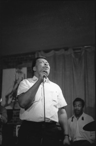 Thumbnail of James Cotton at Club 47: James Cotton singing into a microphone with Francis Clay playing drums at right