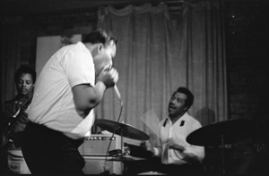 Thumbnail of James Cotton at Club 47: James Cotton playing harmonica into a microphone onstage, with Luther Tucker playing guitar at left and Francis Clay on drums at right
