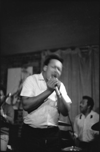 Thumbnail of James Cotton at Club 47: James Cotton holding harmonica and microphone onstage, with guitarist Luther Tucker partly out of frame at left, and Francis Clay playing drums at right