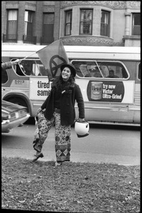 Thumbnail of Vote With your Feet anti-Vietnam War protest march woman holding a motorcycle helmet and showing off her pants