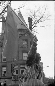 Thumbnail of Vote With your Feet anti-Vietnam War protest march woman in a fur coat sitting on protestor's shoulders and waving a flag