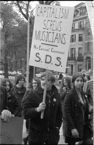 Thumbnail of Vote With your Feet anti-Vietnam War protest march protestor holding sign reading, 'capitalism screws musicians/New England Conservatory/S.D.S'