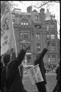 Thumbnail of Vote With your Feet anti-Vietnam War protest march protestors marching and flashing the peace sign while couple watches from balcony