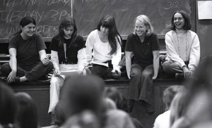 Thumbnail of Women's liberation lecture at Boston University: women on foot of stage, Sue Katz speaking