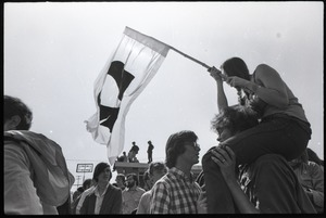 Thumbnail of Antiwar demonstration at Fort Dix, N.J.: woman on shoulder of fellow protester,             waving flag for draft resistance (with omega symbol)