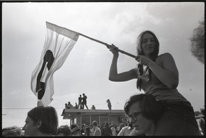 Thumbnail of Antiwar demonstration at Fort Dix, N.J.: woman in shoulders of fellow protester             waving flag for draft resistance (with omega symbol)