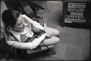 Thumbnail of Young Americans for Freedom (YAF) office: YAF member seated in front of cabinet             adorned with bumper stickers for Reagan, Goldwater, the police, and opposing SDS