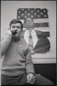 Thumbnail of Young Americans for Freedom (YAF) office: YAF member talking on the phone in             front of poster of William F. Buckley